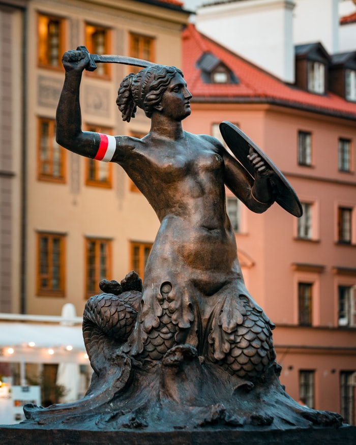Statue of a mermaid holding a sword and shield